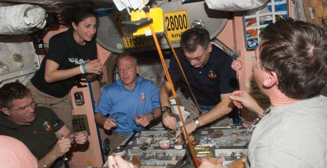 Astronauts share a meal in th eInternational Space Station. Image credit NASA